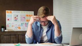 Colaborador cansado do app do móbil cansado no trabalho que tem uma dor de cabeça vídeos de arquivo