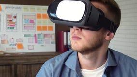 Colaborador móvel do app que testa seu conceito futurista do app usando auriculares de VR video estoque