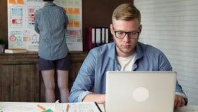 Colaborador móvel do app que trabalha no protótipo móvel novo da aplicação em seu laptop filme