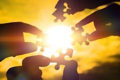 Colaboram quatro mãos que tentam conectar uma parte do enigma com um fundo do por do sol Um enigma à disposição contra a luz sola imagem de stock