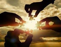 Colaboram quatro mãos que tentam conectar uma parte do enigma com um fundo do por do sol fotos de stock