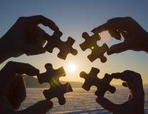 Colaboran cuatro manos que intentan conectar un pedazo del rompecabezas con un fondo de la puesta del sol foto de archivo