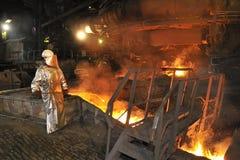 Colada de acero caliente fundida y trabajador Imágenes de archivo libres de regalías