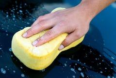 Colada de la mano del coche con la esponja y el jabón amarillos Imagen de archivo