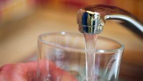 Colada de un vidrio con el agua potable del golpecito de la cocina