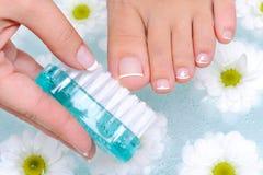 Colada femenina los uñas del dedo del pie a pie Imagenes de archivo