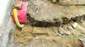 Colada, poniendo el hormigón en las fundaciones de la casa usando la pala del cemento y de las piedras Construyendo, trabajo conc almacen de metraje de vídeo