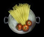 Colador con las pastas y tres tomates Fotos de archivo