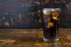 Coladrink, svarta läsk i ett exponeringsglas på tabellen arkivfoton