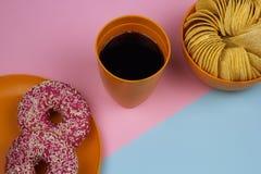 colaexponeringsglas för den bästa sikten, chiper bowlar, munkplattan, rosa färger och blåttbakgrund Arkivfoton