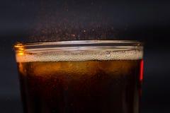 Colaexponeringsglas med iskuber och små droppar som isoleras på svart bakgrund Arkivbild