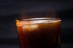 Colaexponeringsglas med iskuber och små droppar som isoleras på svart bakgrund Arkivbilder