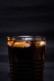Colaexponeringsglas med iskuber och små droppar som isoleras på svart bakgrund Royaltyfri Fotografi