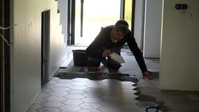 Colagem nivelada do trabalhador manual com as telhas da forma do hexágono da pá de pedreiro e da configuração no assoalho filme