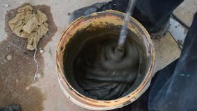 Colagem ou almofariz de mistura do cimento com uma broca longa vídeos de arquivo
