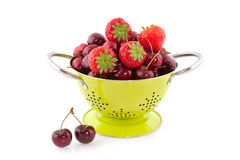 Colander with cherries and strawberries Stock Image
