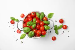 Colander with fresh green basil leaves and cherry tomatoes on white background royalty free stock image
