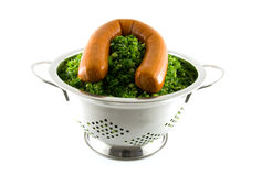 Colander with fresh kale and sausage Royalty Free Stock Photo