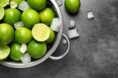 Colander with fresh ripe limes and ice cubes. On gray background, top view Stock Image