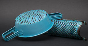 Colander and grater. Two ancient kitchen accessories blue metal Stock Images