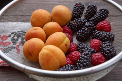 Colander with the washed-up berries raspberry and blackberry and apricots Stock Photography