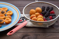 Colander with the washed-up berries raspberry and blackberry and apricots. Kitchen colander grid with the washed red black berries raspberry blackberry and Royalty Free Stock Photography