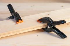 Colando a madeira Duas braçadeiras plásticas da mola que juntam-se a duas partes de cortejam fotografia de stock