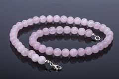Colar cor-de-rosa bonita e luxuosa da pérola de quartzo em um reflexivo Imagens de Stock