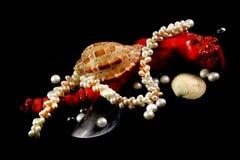 Colar, coral, p?rolas e escudos em um fundo preto fotografia de stock