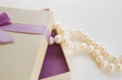 A colar das pérolas pende sobre a caixa de presente Foto de Stock Royalty Free