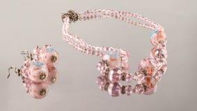 Colar e brincos de cristal brilhantes de encantamento com reflexão em um fundo claro foto de stock