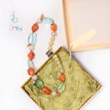 Colar e brincos de pedras naturais em um fundo branco na caixa Imagens de Stock Royalty Free