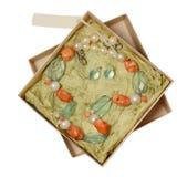 Colar e brincos de pedras naturais em um fundo branco na caixa Fotografia de Stock Royalty Free