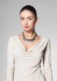 Colar vestindo da mulher bonita no fundo cinzento Imagens de Stock