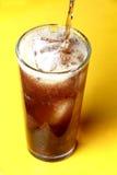 Colasodavatten hällde in i ett exponeringsglas med iskuber Arkivbild