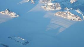 Colata della neve sulle colline sopra l'acqua congelata video d archivio