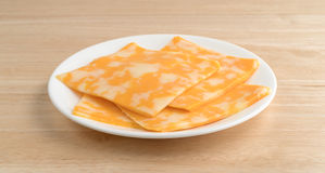 Colby-Jack cheese slices on a plate atop table Royalty Free Stock Photos