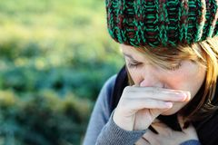Cold. Woman with hat has to sneeze royalty free stock image