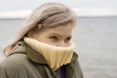 Cold!. Really cold! A blond girl in a coat and sweater portrait on cold wind. Lake in a background Stock Photos