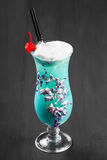 Cold alcoholic blue cocktail, decorated with berries and flowers in glass on black wooden background Royalty Free Stock Photography