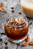 Cold alcoholic cocktail with coffee, cognac and ice in glass on wooden background. Royalty Free Stock Photo