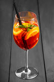 Cold alcoholic cocktail with cola, ice, mint and orange in wineglass on wooden background Royalty Free Stock Photo