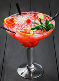 Cold alcoholic watermelon cocktail with orange, mint, ice and grapes in big wineglass on black wooden background Royalty Free Stock Photography