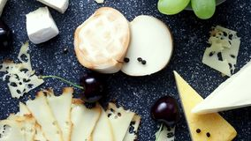 Cold appetizer. Cold cuts. Cheese on cutting board, top view. 4k resolution stock video footage