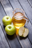 Cold apple juice in pitcher on table, vertical top view morning still life Royalty Free Stock Photography