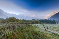 Cold atumn morning at sunrise with Julian Alps in background. Autumn clouds dolomites fall fog frost grass italy landscape mangart mist mountain range mountains stock images