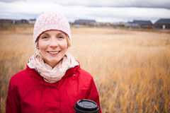 Cold Autumn Day with a Coffee. Handsome Happy Woman in a Field during cold Autumn Day with a Coffee stock photography