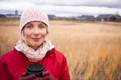 Cold Autumn Day with a Coffee. Handsome Happy Woman in a Field during cold Autumn Day with a Coffee stock photos