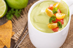 Cold avocado soup with tomato salsa Stock Photo