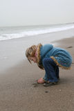 Cold Beach. Girl taking sand on a cold beach stock images